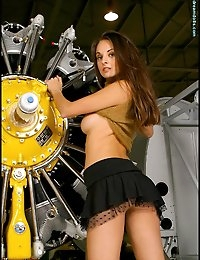 Fast, sleek, and giving off some strong heat--that's Sanya, who rivals the jet engine she's standing by in terms of sheer power. With the engine on blocks, Sanya tries to rev it up with her erotic touch. She fondles the hardware as she twirls around in her miniskirt and gold top, her pretty round ass and legs a spectacle more inspiring than any jet. Well, just sit back and feel the G-force from this ravishing brunette as Sanya Strokes Her Engine