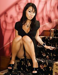 Asa Akira poses in black lingerie on a dark lovely staircase.