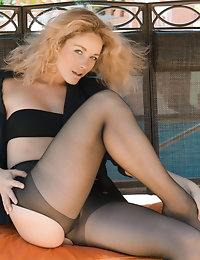 Sweet blonde beauty Madonna in black stockings posing nude on the swings