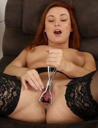 Stunning redhead in stockings stretches her pussy